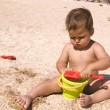Serious tanned boy playing on beach — Stock Photo #1144634