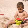Serious tanned boy playing on the beach - Stock Photo