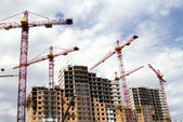Building cranes and building houses — Stock Photo