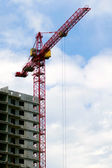 Building crane aganist cloudy sky and bu — Stock Photo