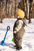 Thoughtful baby with shovel against snow — Foto de Stock