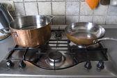 Pan and frying-pan at a gas-stove — Stock Photo