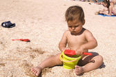 Serious tanned boy playing on the beach — Stock Photo