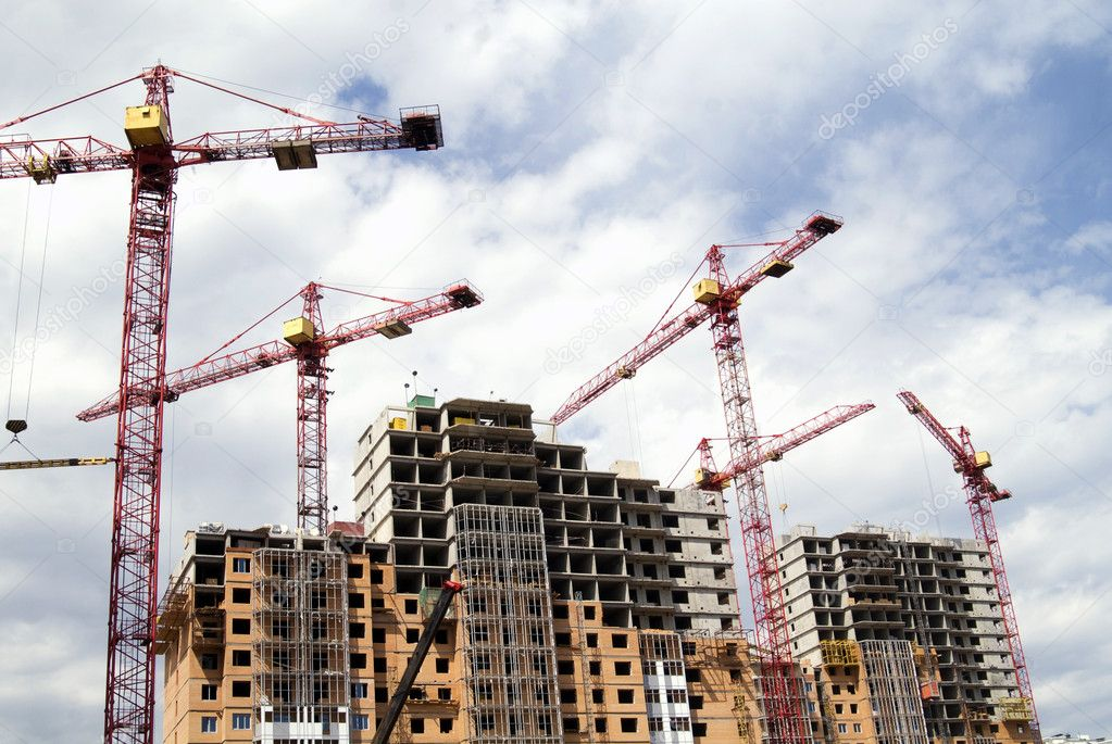 Building cranes against blue sky and buildings — Stok fotoğraf #1144183