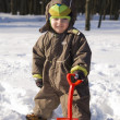 Baby with red shovel against snow — Stock Photo