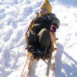 Baby in green coat has rest in sled — Stock Photo #1165321