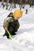 Baby with green shovel against snow — Stock Photo