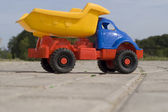 Baby toy dump truck on sunny road — Stock Photo