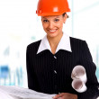 Female architect holding blueprints — Stock Photo