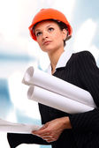 Female architect holding blueprints — Stockfoto