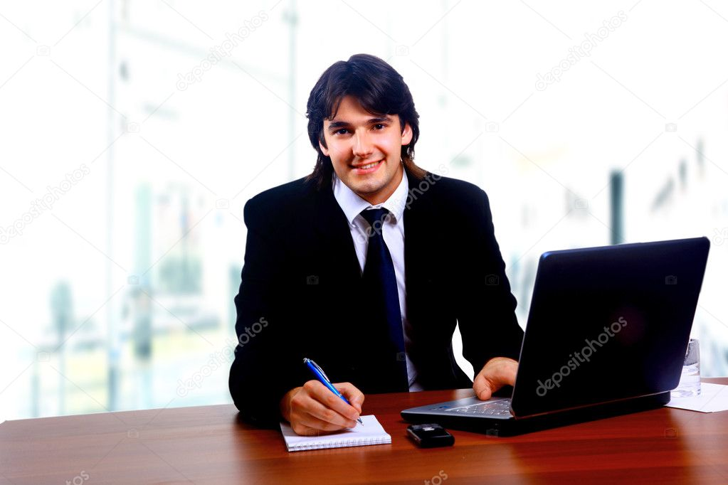 Businessman sitting by desk at office working on the laptop  Stock Photo #1148147