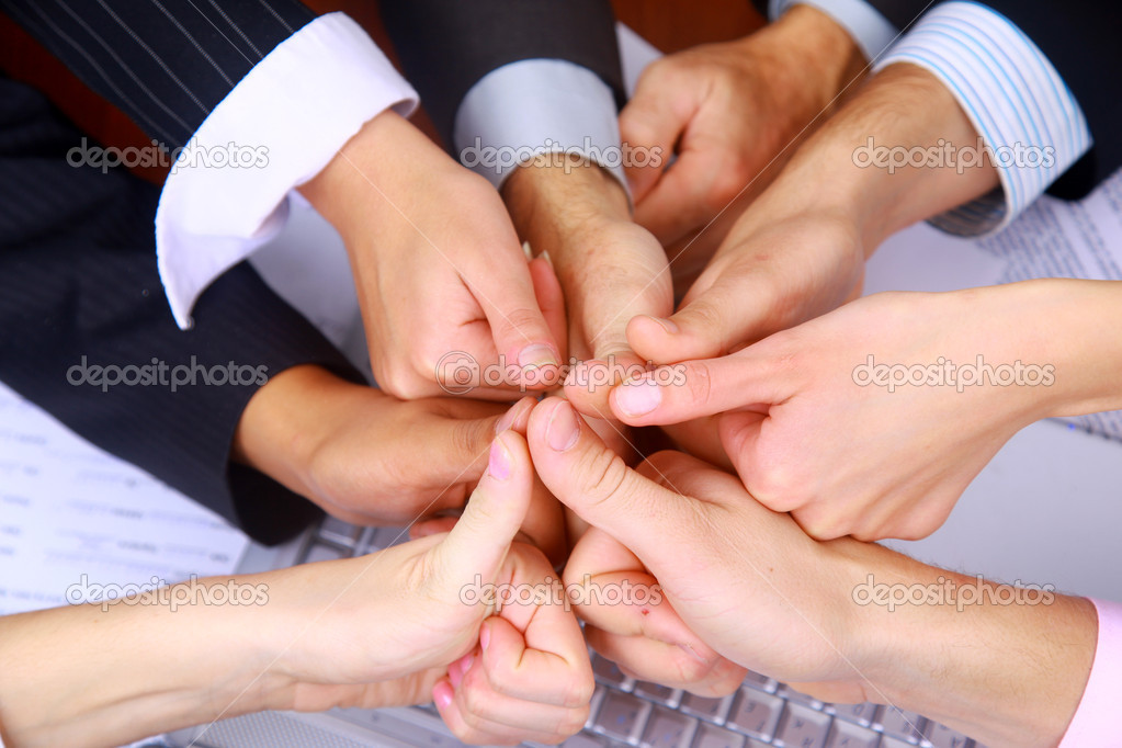 Group of business making a pile of hands in a light and modern office environment — Stock Photo #1148707