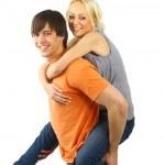 Piggybacking - Happy young teenaged couple enjoying themselves against whit — Stock Photo