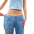 Happy young woman in old jeans pant after losing weight — Stock Photo