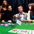Stylish man in black suit folds two cards in casino poker at Las Vegas over - ストック写真