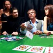 Stylish man in black suit folds two cards in casino poker at Las Vegas over - Stock Photo