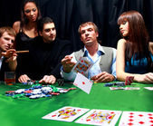 Stylish man in black suit folds two cards in casino poker at Las Vegas over — Stock Photo
