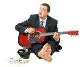 Businessman playing guitar — Stock Photo