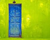 Blue Door in Shabby Green Wall — Stock Photo