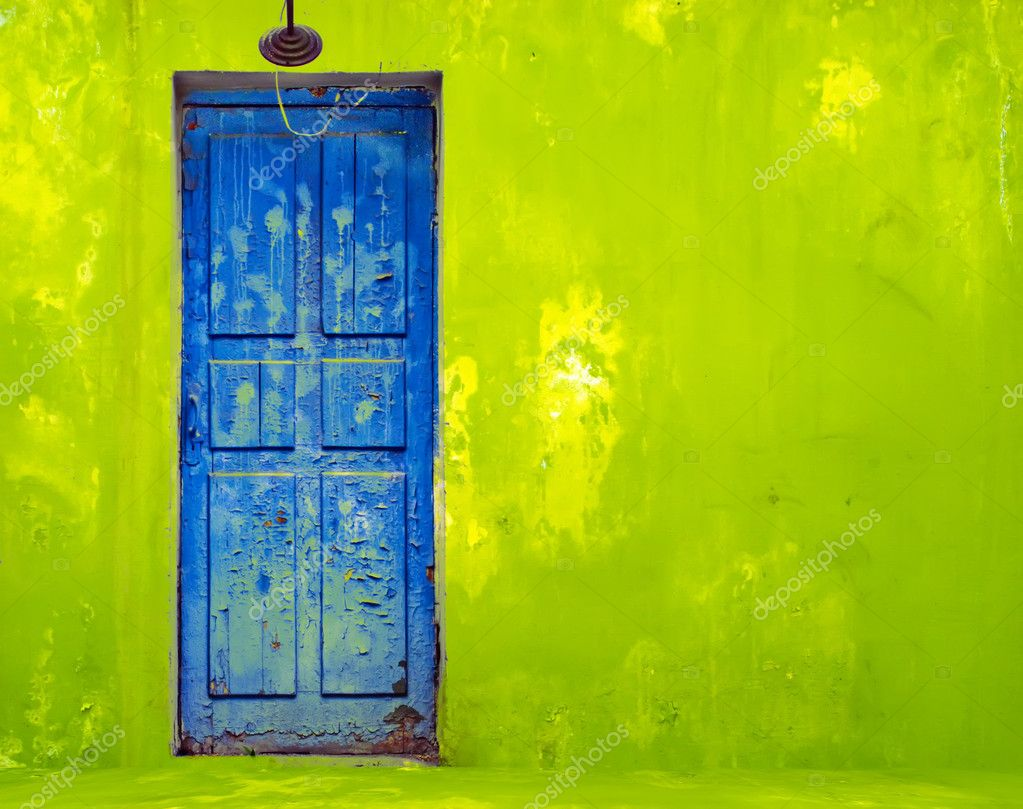 Blue Door in Shabby Green Wall — Stock Photo #1154110