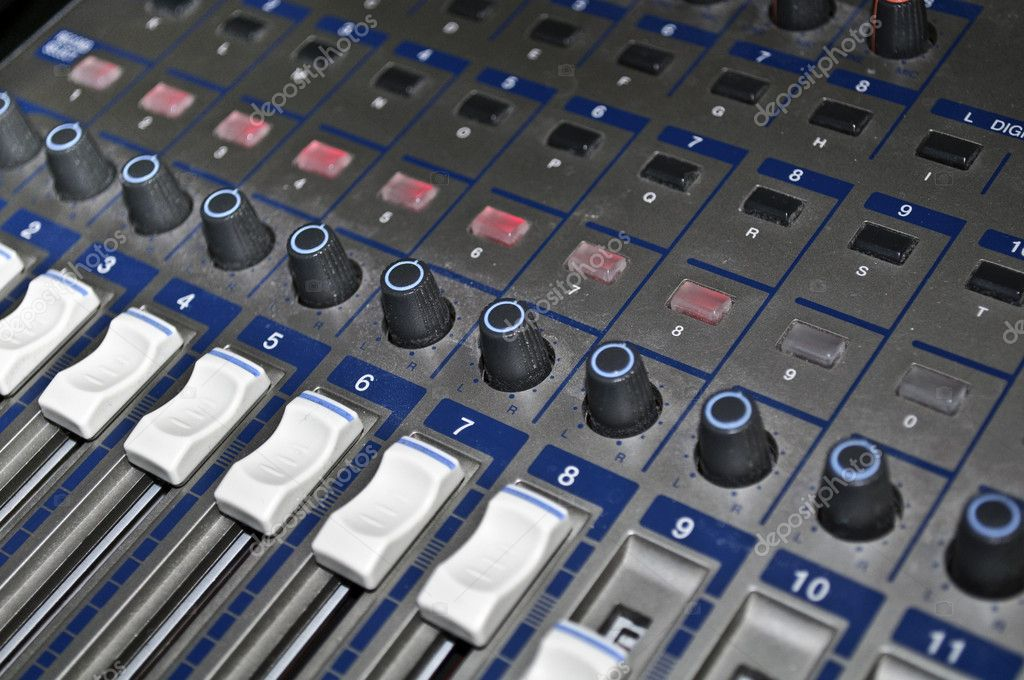 A mixing console with faders and controls.  Stock Photo #1583072
