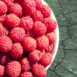 Juicy Raspberries On Tree Stump — Stock Photo #2429111