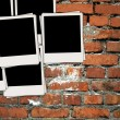 Pile of Blank Photos on Brick Wall - Stock Photo