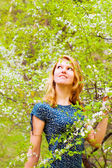 Young woman and flowered tree — Stock Photo
