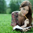 Woman lays on a grass in park with a diary in hands — Stockfoto
