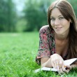 Woman lays on a grass in park with a diary in hands — Stock Photo