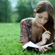 Woman lays on a grass in park with a diary in hands — ストック写真