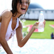 Young woman drinks mineral water — Stock Photo