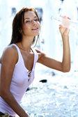 Mladá žena pije minerálku — Stock fotografie
