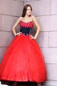 Beautiful woman in a red Gothic dress — Stock Photo