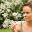 Young woman blowing on the dandelion — Stock Photo