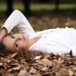 Beautiful girl lies on the earth, oak leaves — Stock Photo