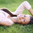 Royalty-Free Stock Photo: Cute young female lying on grass field at the park