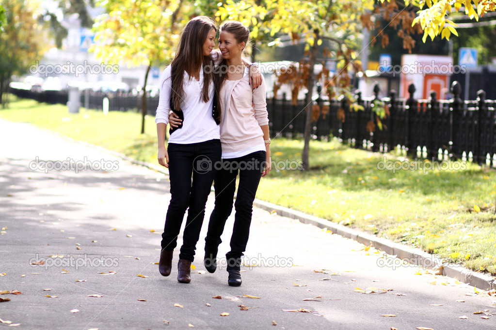 Fashionable girls twins walk in the street  Stock Photo #1326617