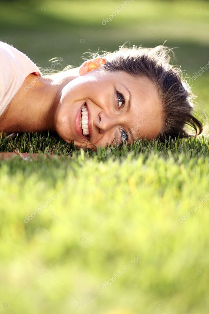 Cute young female lying on grass field at the park  — Stock Photo #1326640