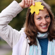 Brunette with golden autumn leaf — Stock Photo #2497873