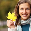 Stock Photo: Brunette with golden autumn leaf