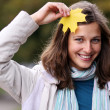 Brunette with golden autumn leaf — Stock Photo