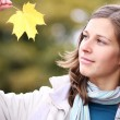 Brunette with golden autumn leaf — Stock Photo #2497936