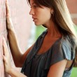 Beautiful woman standing against wall — Stock Photo #2498680