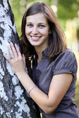 Happy girl at a white birch — Stock Photo