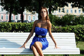 Mujer tiene un descanso sentado en un banco — Foto de Stock