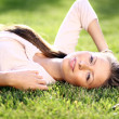 Cute young female lying on grass field at the park — Stock Photo