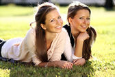 Beautiful twins of sister lays on green — Stockfoto