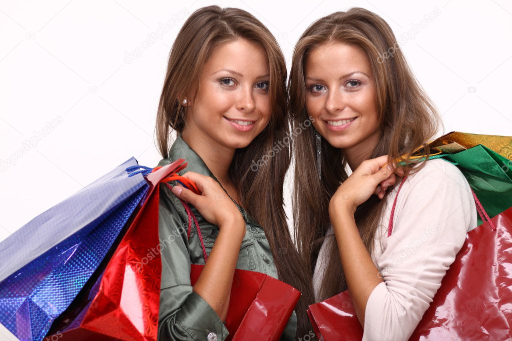 Twins sisters holding shopping bags on white isolated  — Stock Photo #2518915
