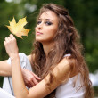 Beautiful young woman in autumn park — Stockfoto